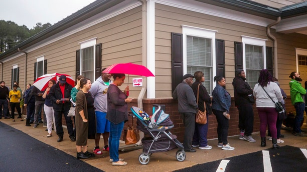 Voters wait to cast their ballots outside the Ivy Community Center in Durham, N.C. State officials report there are issues with ballot tabulators due to high humidity.