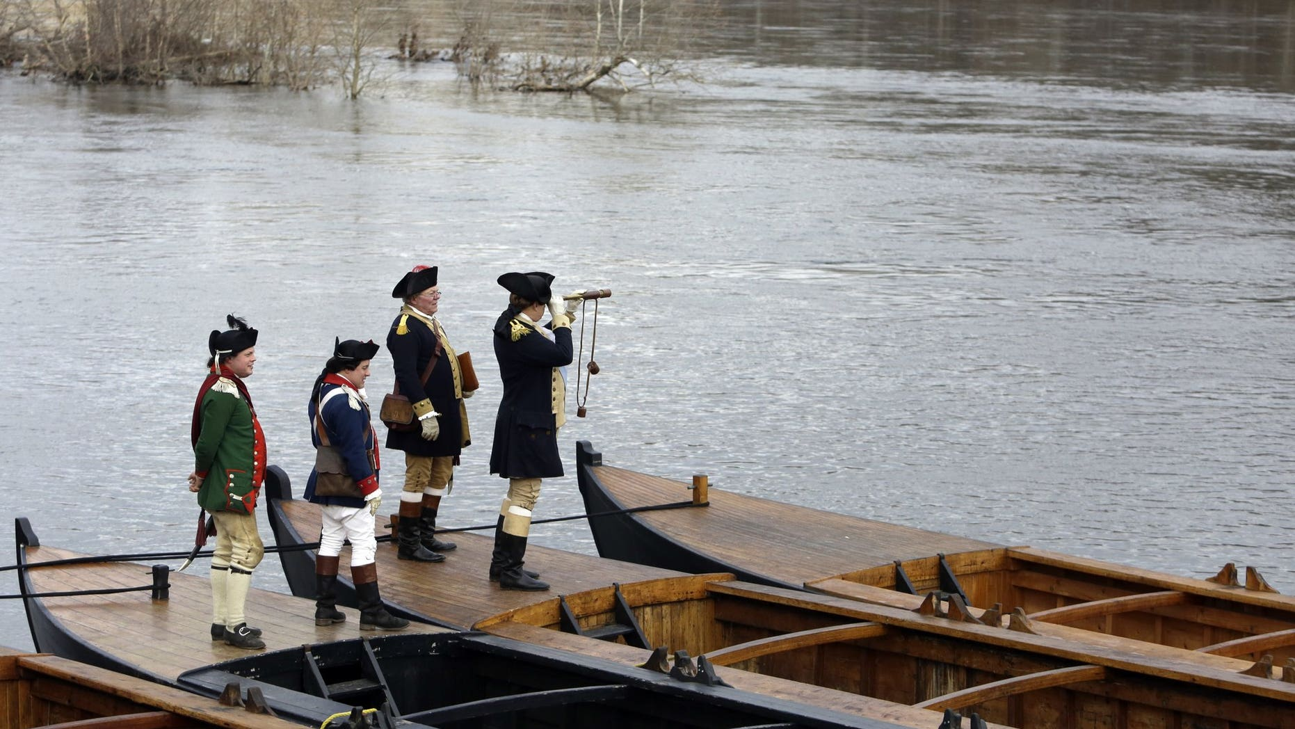 Re-enactor John Godzieba, right, portrays Gen. George Washington as he peers across the Delaware River, Tuesday Dec. 25, 2018 in Washington Crossing, Pa. The annual reenactment of George Washington's daring 1776 crossing of the Delaware River on Christmas Day has once again been left high and dry as organizers announced Monday that the river crossing portion of the reenactment will not take place due to high river conditions following recent rainfall. Other activities carried on as scheduled.