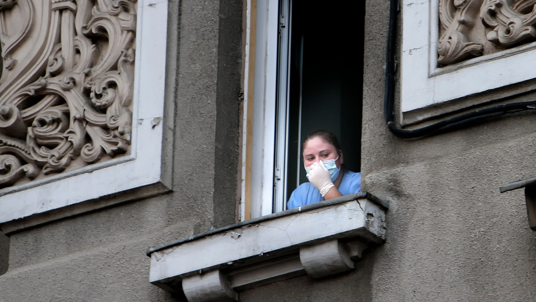 In this Aug. 16, 2010 file photo a nurse looks on from a window of the Giulesti hospital following a fire that left 5 newborn babies dead.