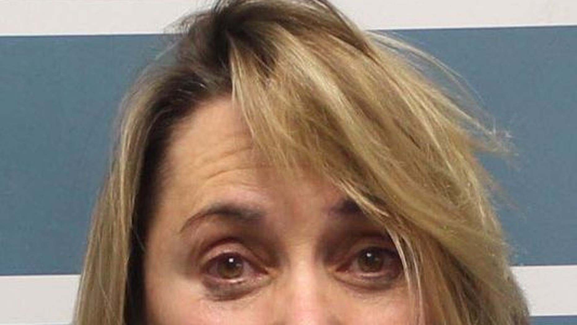 "Margaret Gieszinger, 52, was arrested after she was seemingly caught in a video cutting hair off a student's head while incorrectly singing ""The Star-Spangled Banner."""