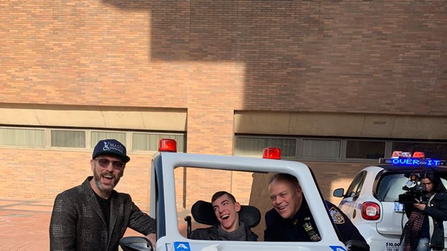 Aidan Riley, pictured with his police officer father and David Vogel, regional director of Magic Wheelchair, received his customized car on Wednesday.