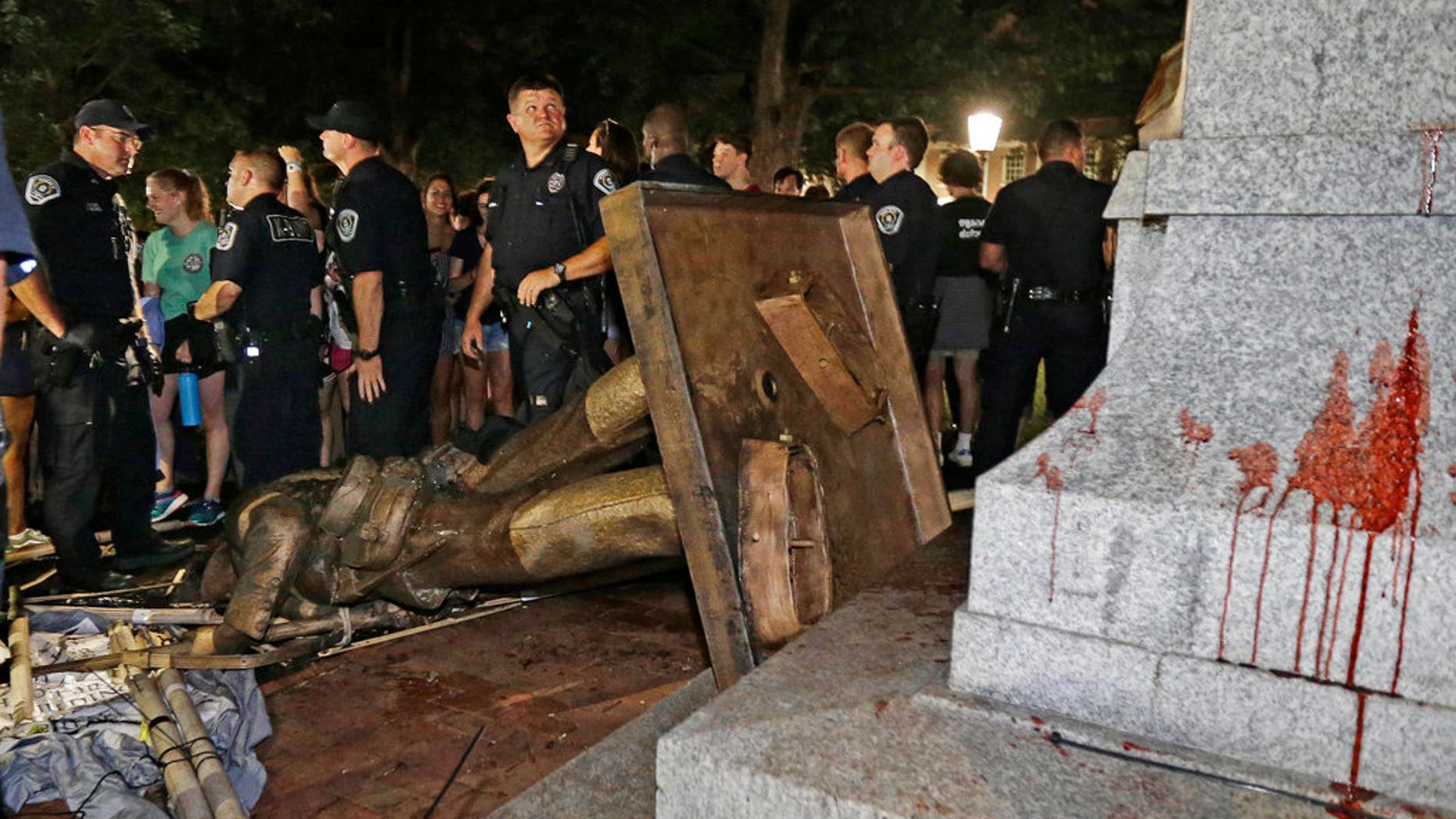 "In this Aug. 20, 2018 file photo, police stand guard after the Confederate statue known as Silent Sam was toppled by protesters on campus at the University of North Carolina in Chapel Hill, N.C. A plan to move ""Silent Sam"" presented by the school on Monday sparked protests hours after campus trustees overwhelming approved the proposal.<br data-cke-eol=""1"">"