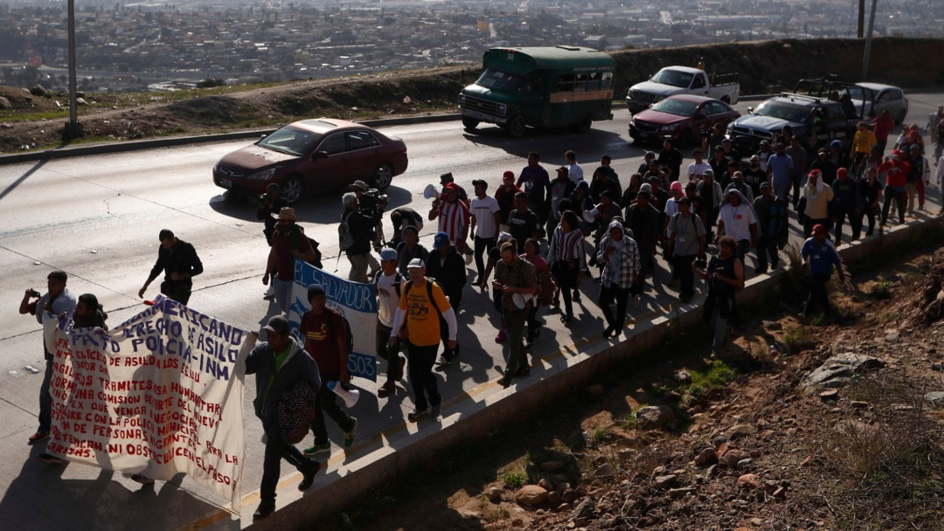 Central American migrants march to the U.S. consulate in Tijuana, Mexico, Tuesday, Dec. 11, 2018. [AP Photo/Moises Castillo)