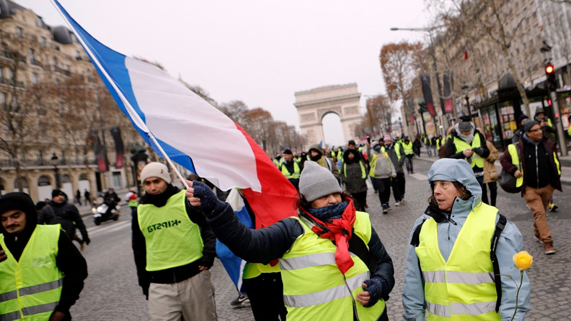 """Demonstrators wearing yellow vests walk down the Champs-Elysees avenue, Saturday, Dec. 15, 2018 in Paris. A strong police presence has deployed in Paris before planned demonstrations by the """"yellow vest"""" protesters, with authorities repeating calls for calm after previous violent protests and rioting."""