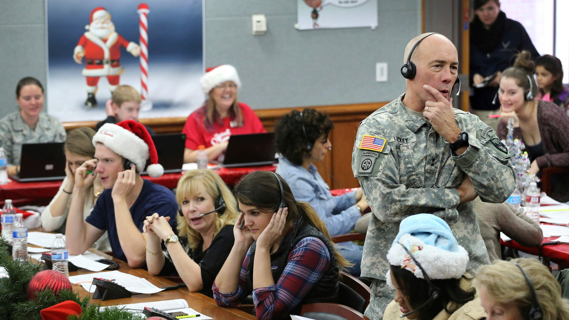 In this Dec. 24, 2014, file photo, NORAD Chief of Staff Maj. Gen. Charles D. Luckey takes a call while volunteering at the NORAD Tracks Santa center at Peterson Air Force Base in Colorado Springs, Colo. Hundreds of volunteers will help answer the phones from children around the world calling for Santa when the program resumes on Monday, Dec. 24, 2018, for the 63rd year. (AP Photo/Brennan Linsley, File)