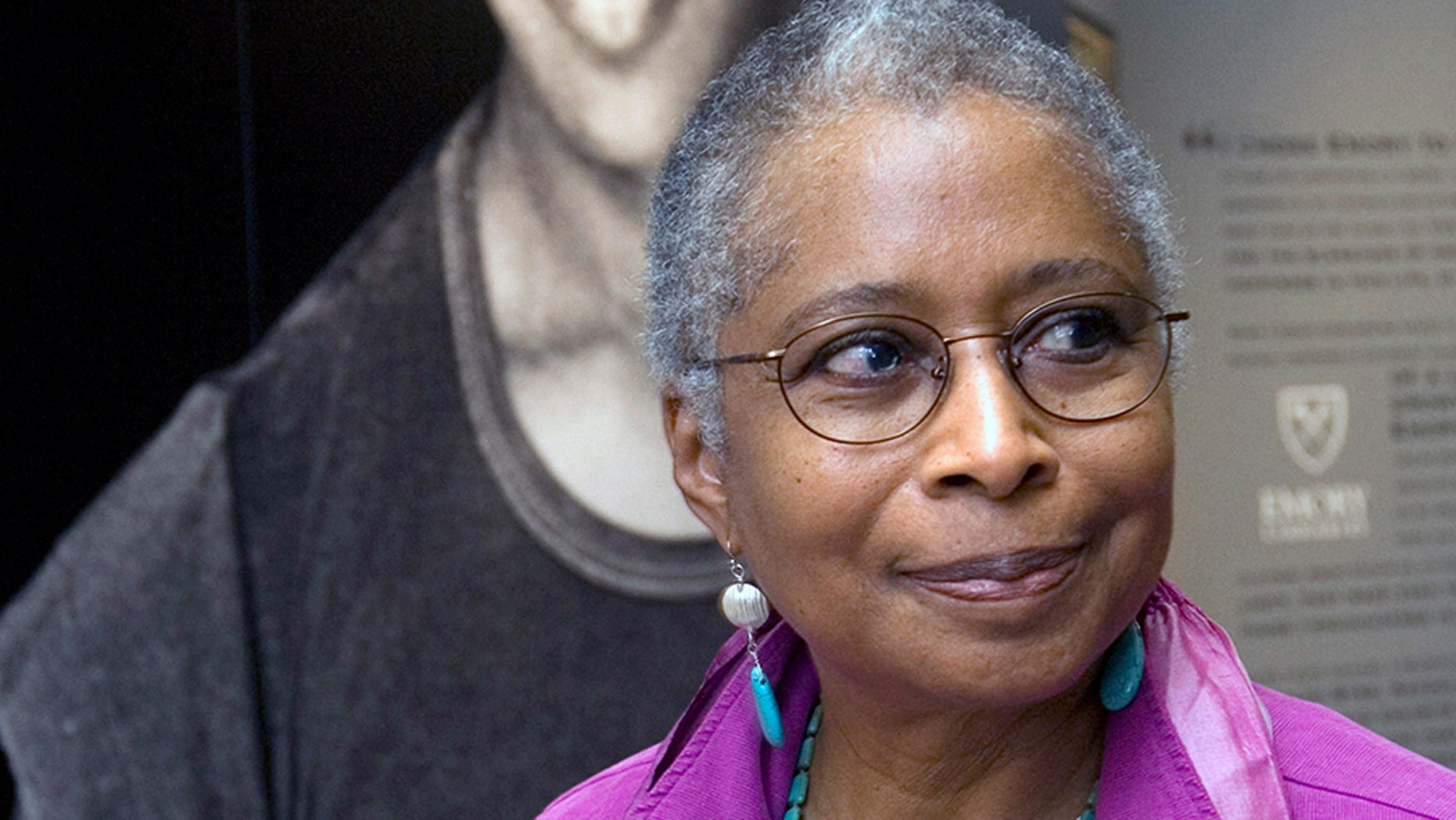FILE - In this April 23, 2009 file photo, Alice Walker stands in front of a picture of herself from 1974 as she tours her archives at Emory University, in Atlanta. (AP Photo/John Amis, File)