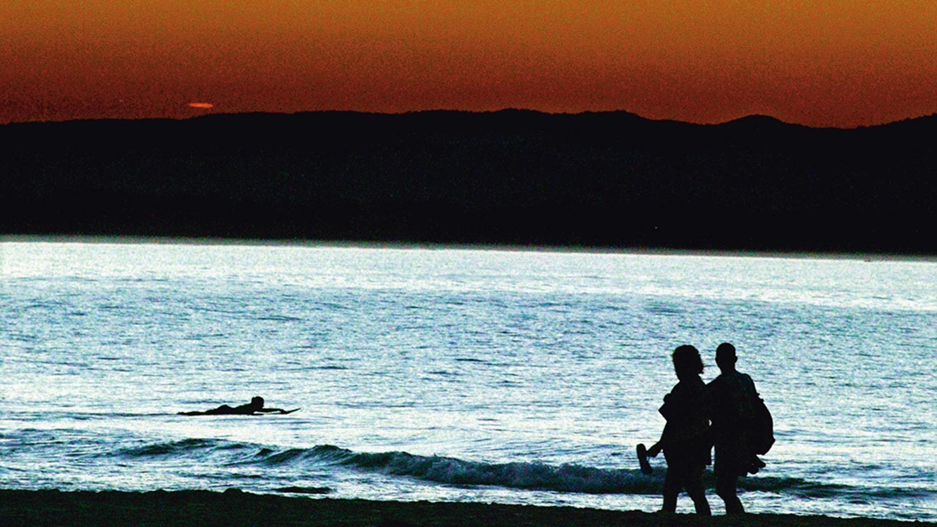 A couple stroll along a Byron Bay beach at sunset.