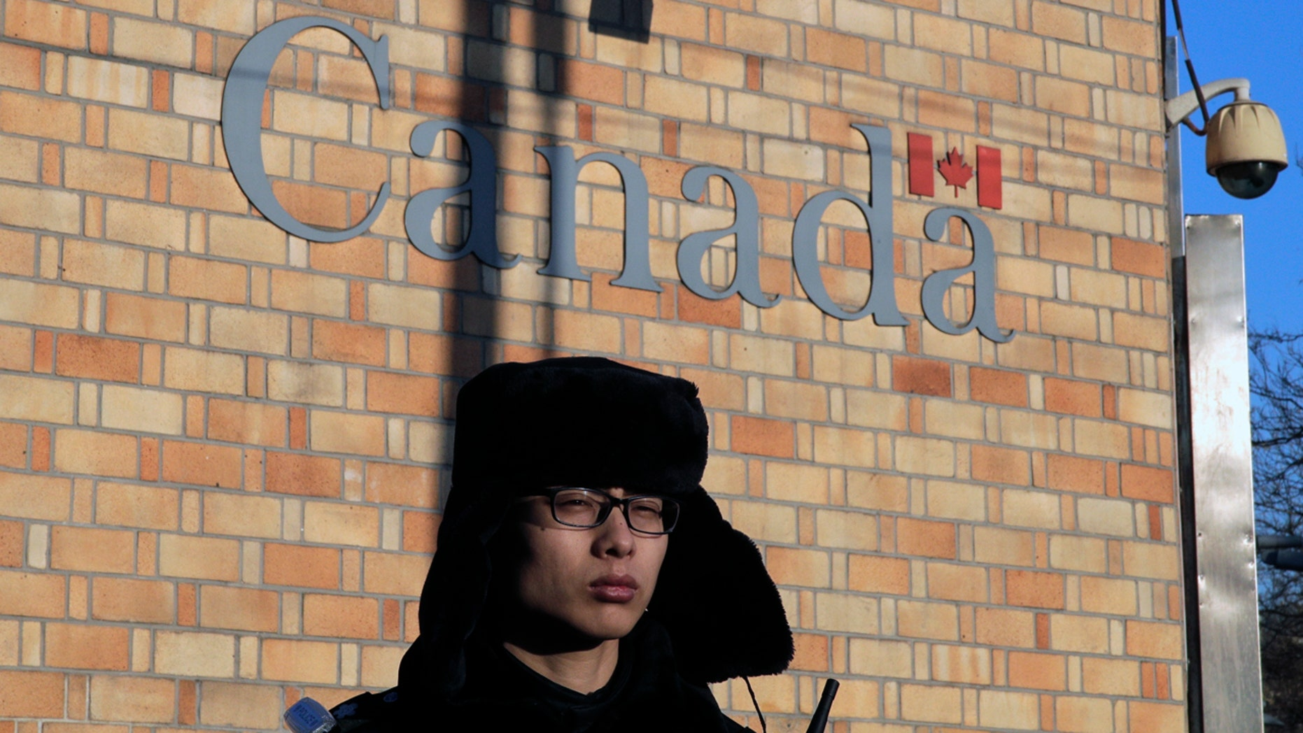 A policeman stands watch outside the Canadian Embassy in Beijing, Wednesday, Dec. 12, 2018. A Canadian court granted bail on Tuesday to a top Chinese executive arrested at the United States' request in a case that has set off a diplomatic furor among the three countries and complicated high-stakes U.S.-China trade talks. (AP Photo/Andy Wong)