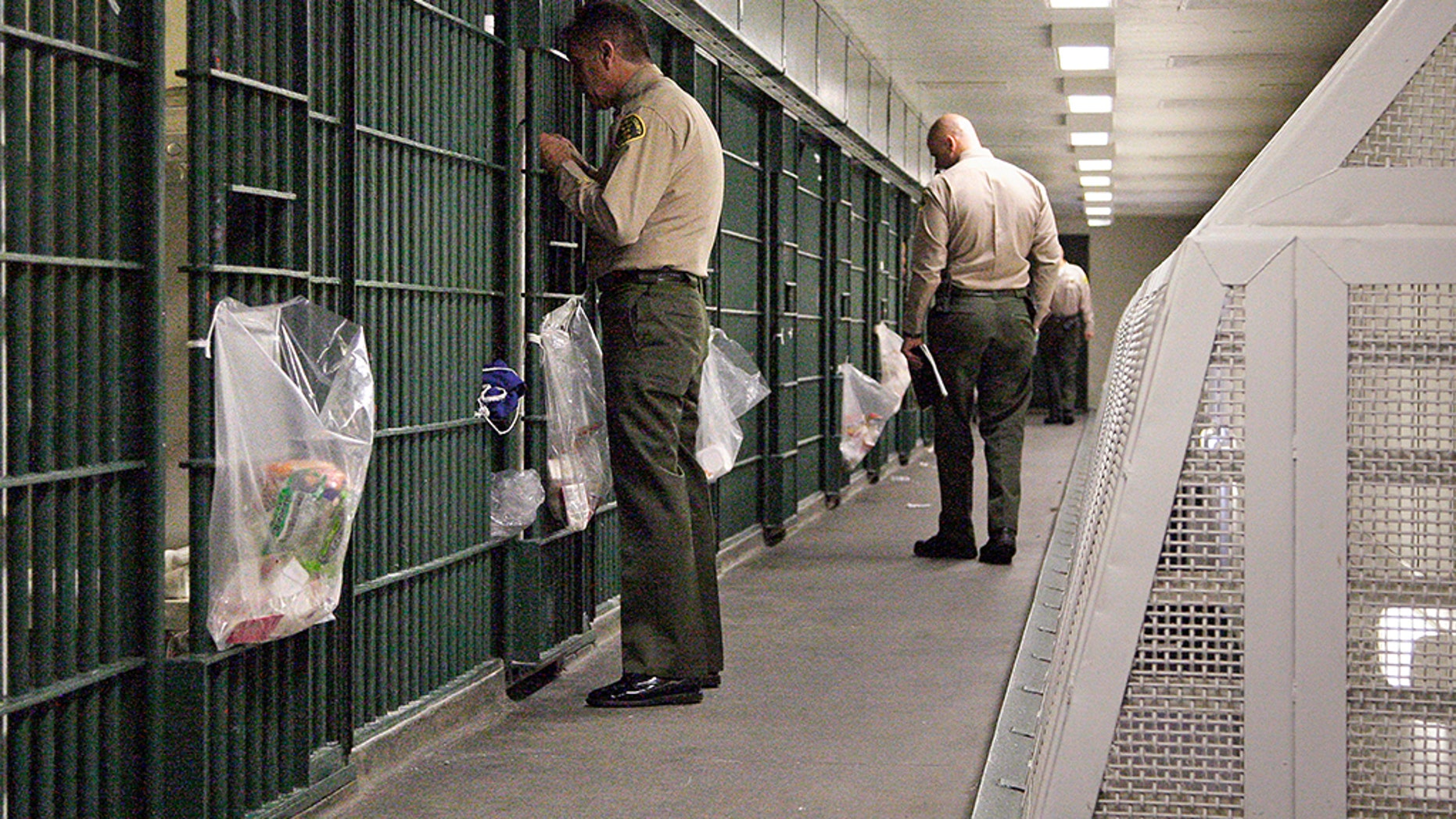 In this Oct. 3, 2012 file photo, Los Angeles County Sheriff's deputies inspect a cell block at the Men's Central Jail in downtown Los Angeles. Five deputies were hospitalized after they were attacked by inmates at the jail on Thursday.