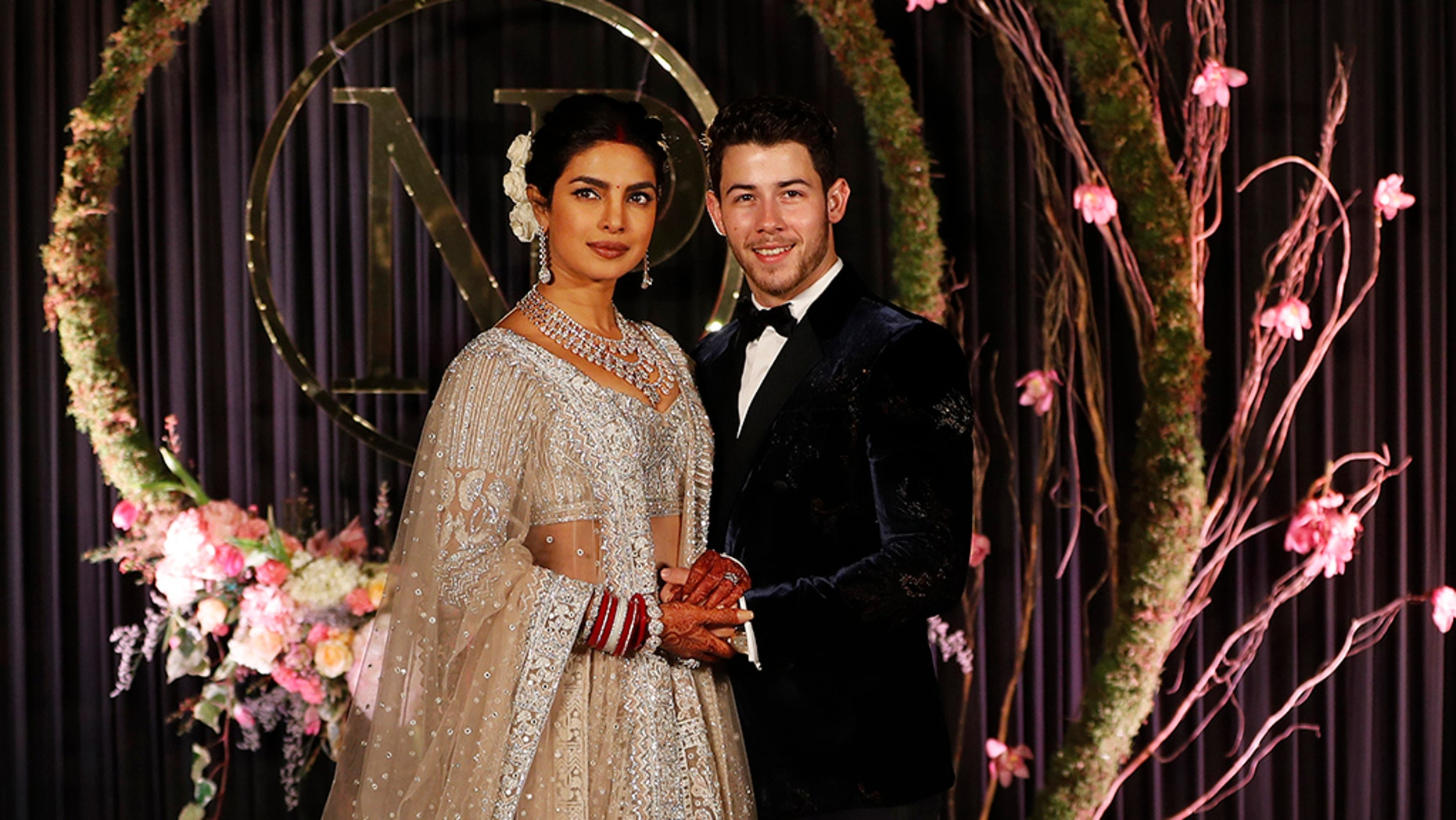 Bollywood actress Priyanka Chopra and musician Nick Jonas stand for photographs at their wedding reception in New Delhi, India, Tuesday, Dec. 4, 2018. (AP Photo/Altaf Qadri)