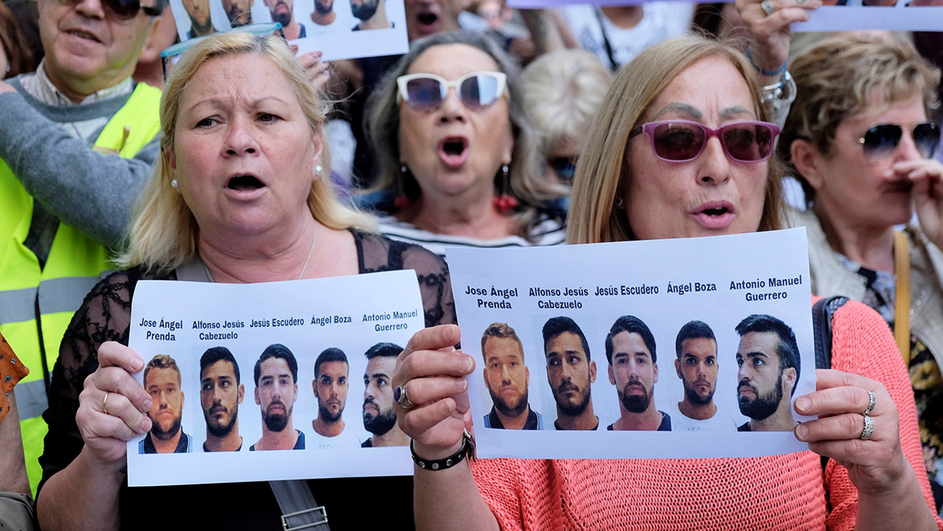 People shout slogans while holding signs during a protest outside the City of Justice, after a Spanish court on Thursday sentenced five men accused of the group rape of an 18-year-old woman at the 2016 San Fermin bull-running festival each to nine years in prison for the lesser charge of sexual abuse, in Valencia, Spain April 27, 2018. REUTERS/Heino Kalis? - RC121CBBB710