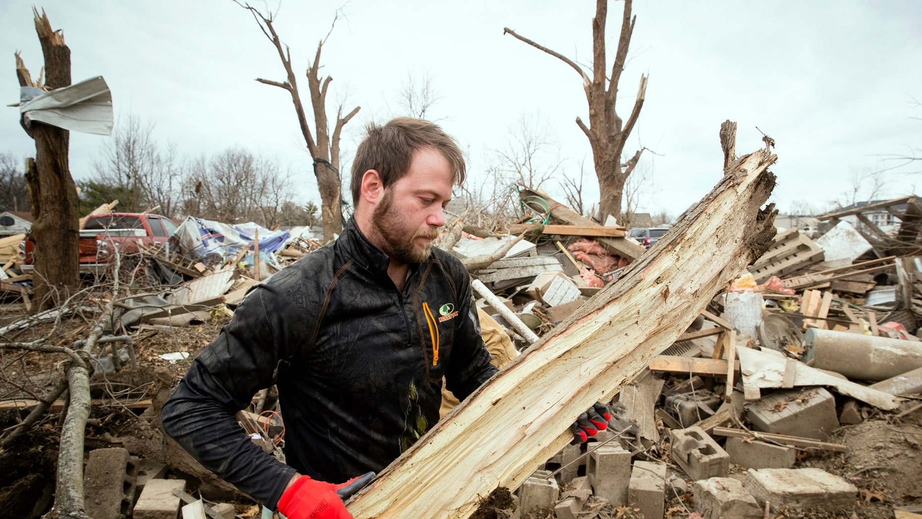 Steven Tirpak cleans debris from the remains of his two-story home in Taylorville, Ill., Sunday, Dec. 2, 2018. Tirpak and his infant were not home when the storm struck. The National Weather Service says multiple tornadoes touched down in central Illinois, damaging dozens of structures and injuring multiple people. (Ted Schurter/The State Journal-Register via AP)