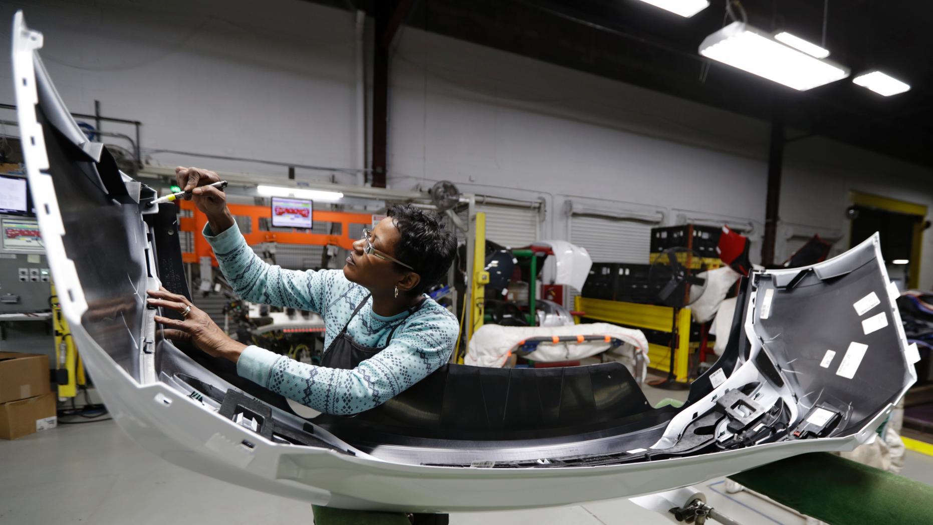 FILE- In this Nov. 28, 2018, file photo final inspector Mary Skinner inspects the rear end of a General Motors Chevrolet Cruze at Jamestown Industries in Youngstown, Ohio. On Monday, Dec. 3, the Institute for Supply Management, a trade group of purchasing managers, issues its index of manufacturing activity for November. (AP Photo/Tony Dejak, File)