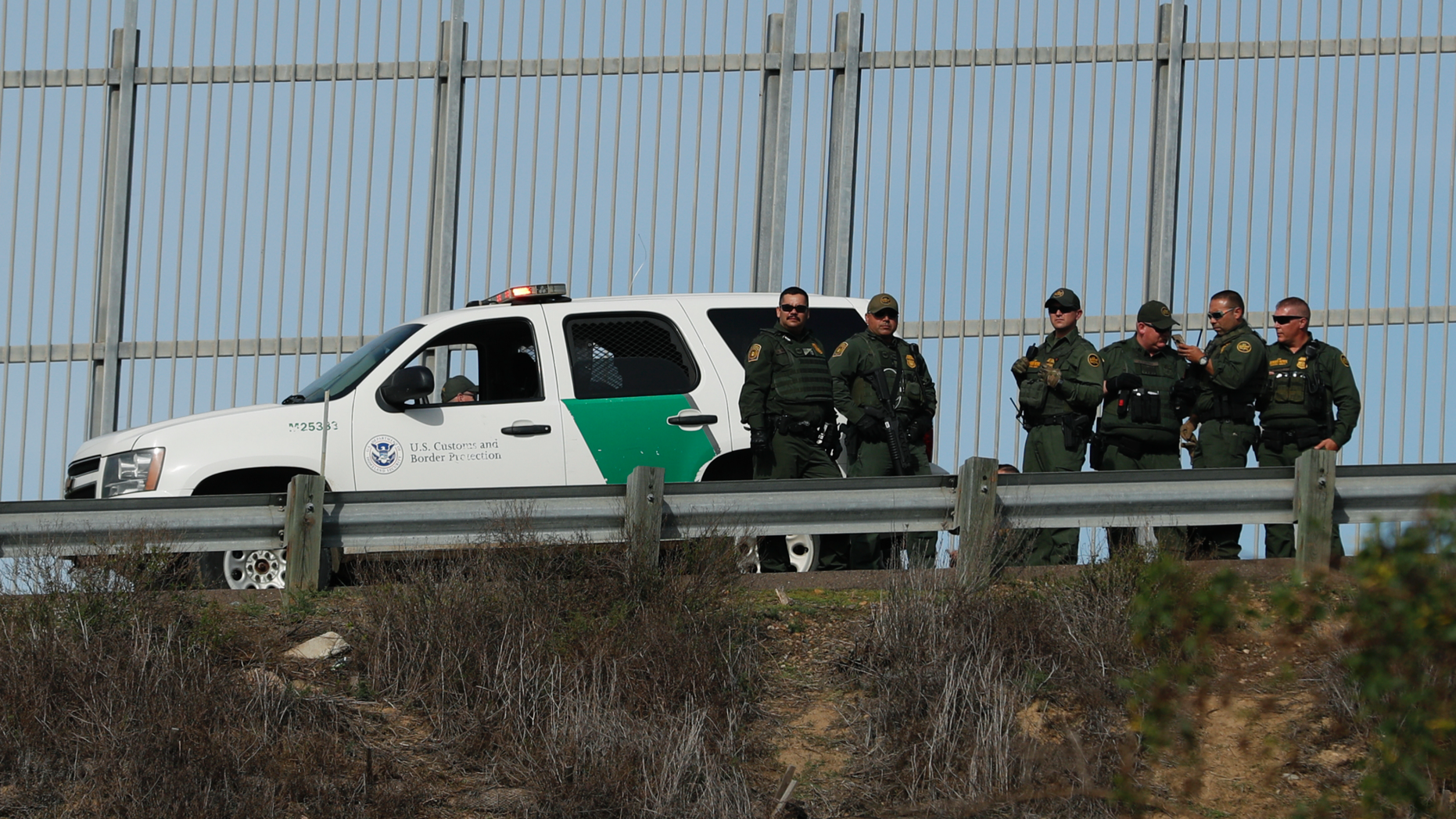 U.S. Border Patrol agents stand in front of a secondary fence in San Diego, California looking across border wall toward Mexico as they respond to a group of Central American migrants who crossed the border wall illegally, seen from across the wall in Tijuana, Mexico, Sunday, Dec. 9, 2018. Discouraged by the long wait to apply for asylum through official ports of entry, many Central American migrants from recent caravans are choosing to cross the U.S. border wall illegally and hand themselves in to Border Patrol agents to request asylum. (AP Photo/Rebecca Blackwell)