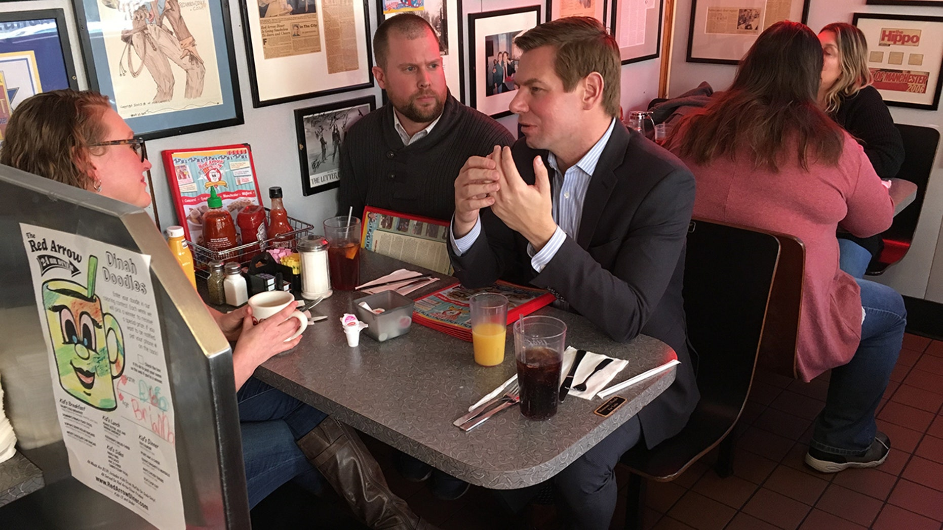 Congressman Eric Swalwell speaks with two New Hampshire Democratic state representatives at the Red Arrow Diner in Manchester.
