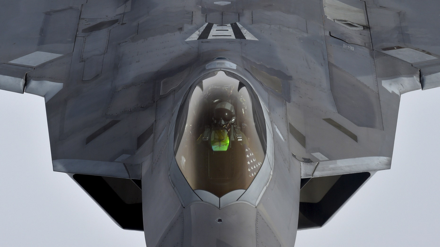 File photo - A pilot looks up from a U.S. F-22 Raptor fighter as it prepares to refuel in mid-air with a KC-135 refueling plane over European airspace during a flight to Britain from Mihail Kogalniceanu air base in Romania April 25, 2016.