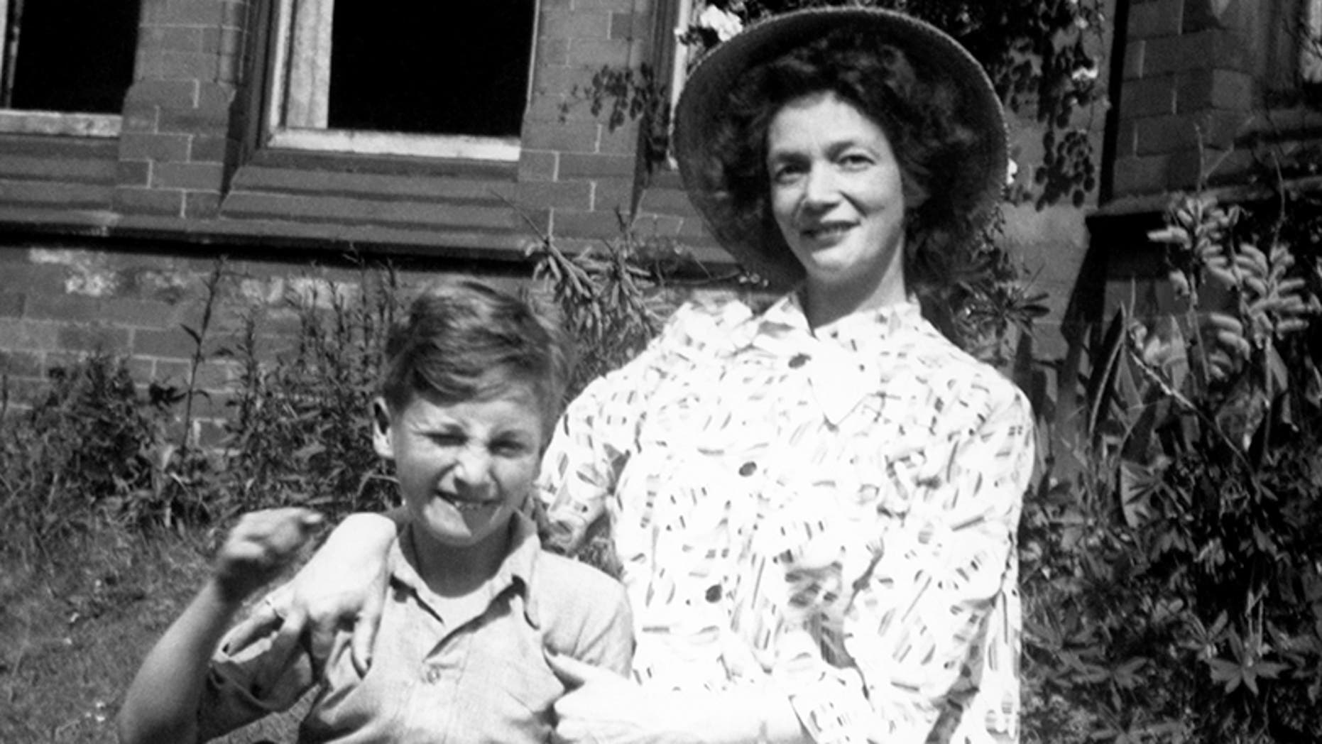 "Nine year old John Lennon (1940-1980) poses for a portrait with his mother Julia (1914-1958) in the front garden of ""Ardmore,"" which was the name of the home of John's cousin, Stanley Parkes circa 1949 in Rock Ferry, Cheshire, England."