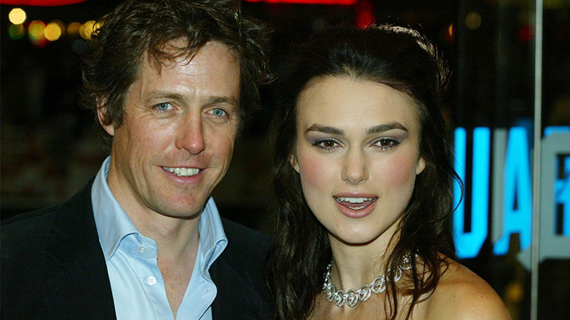 """Actors Hugh Grant and Kiera Knightley attend the UK charity film premiere of """"Love Actually"""" at The Odeon Leicester Square on November 16, 2003 in London."""