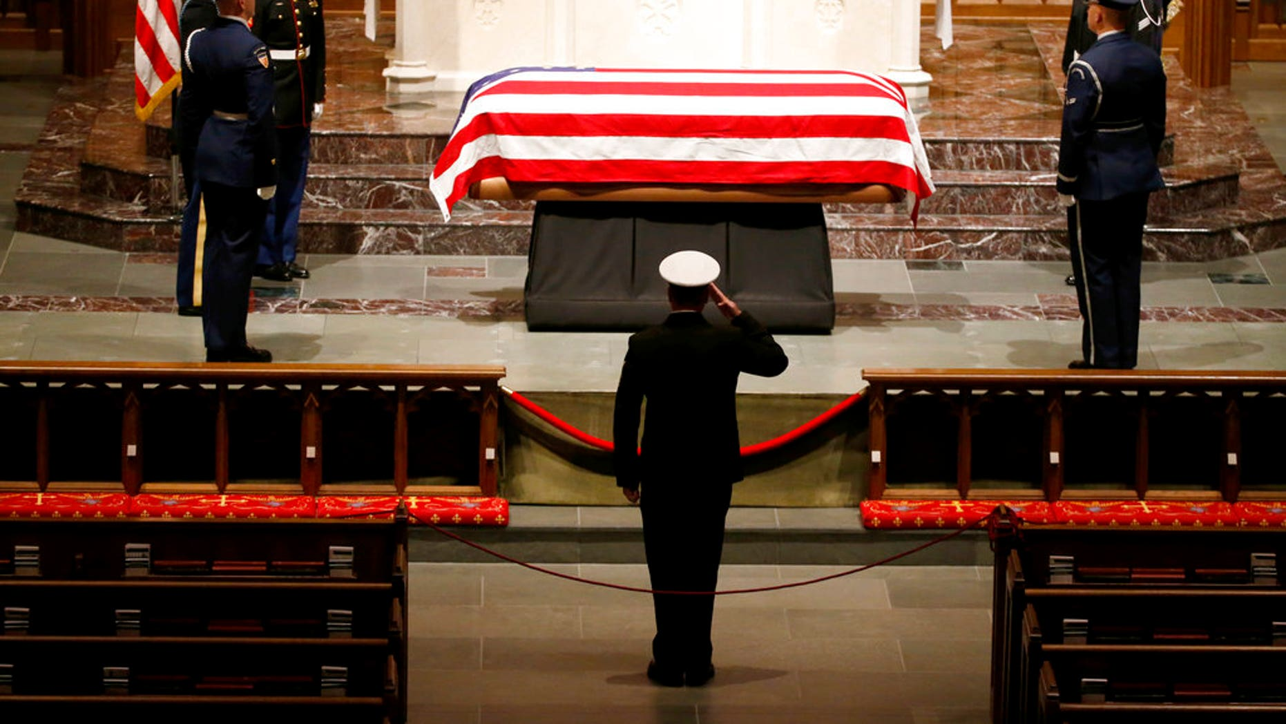 A member of the military pays his respects to the flag-draped casket of former President George H.W. Bush at St. Martin's Episcopal Church Wednesday, Dec. 5, 2018, in Houston. (AP Photo/Mark Humphrey)