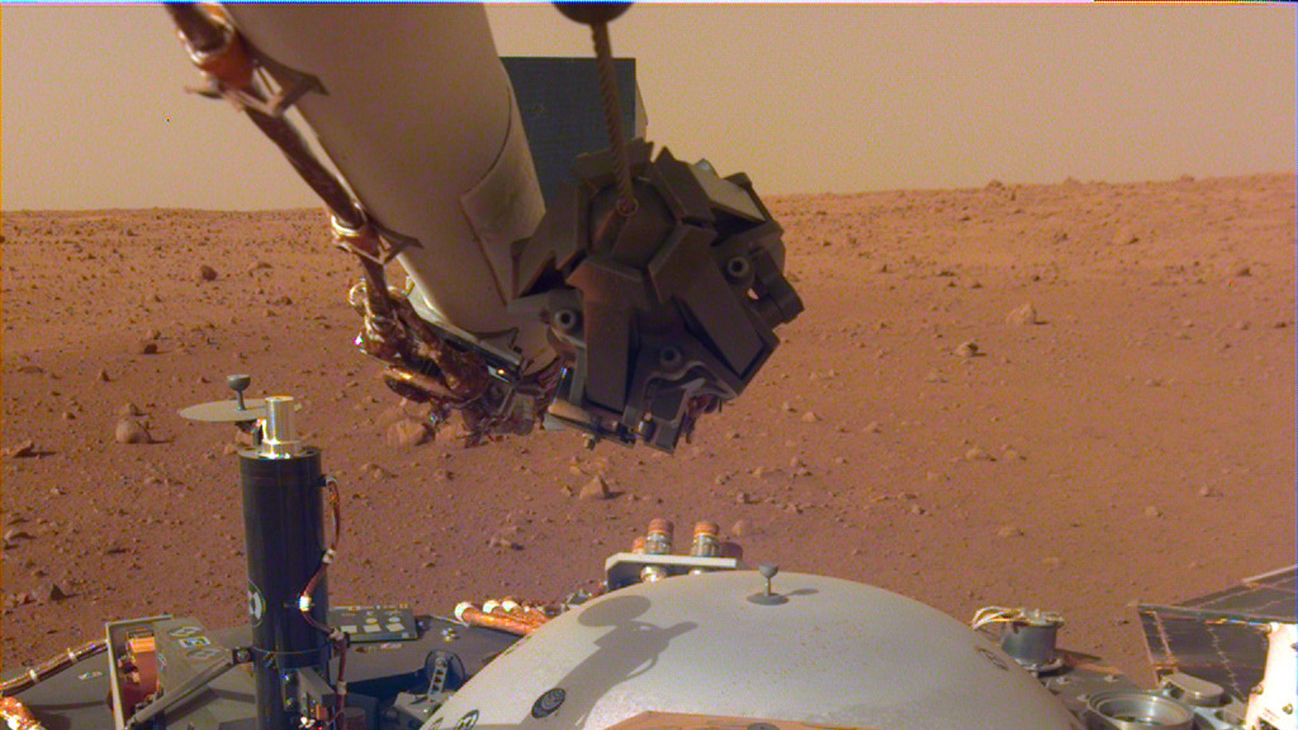 This image from InSight's robotic-arm mounted Instrument Deployment Camera shows the instruments on the spacecraft's deck, with the Martian surface of Elysium Planitia in the background. (Credit: NASA/JPL-Caltech)