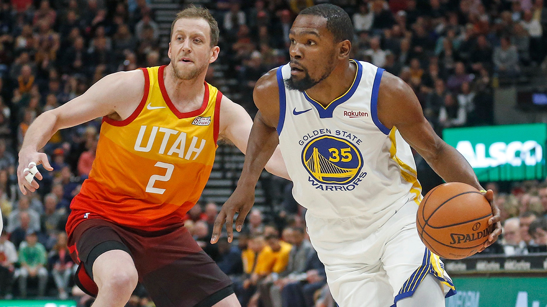 Golden State Warriors forward Kevin Durant (35) drives around Utah Jazz forward Joe Ingles (2) in the first half during an NBA basketball game Wednesday Dec. 19, 2018, in Salt Lake City. (Associated Press)