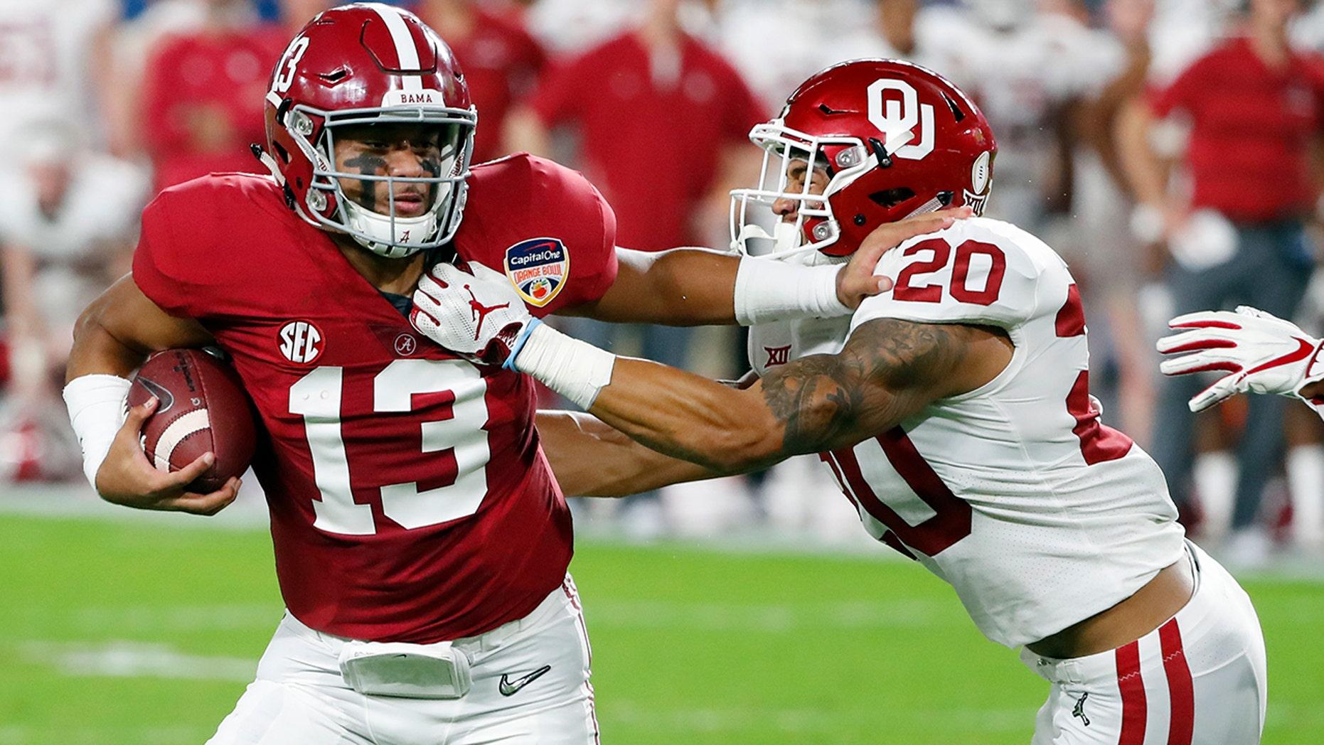 Alabama quarterback Tua Tagovailoa (13) fights off Oklahoma safety Robert Barnes (20), during the first half of the Orange Bowl NCAA college football game, Saturday, Dec. 29, 2018, in Miami Gardens, Fla. (AP Photo/Wilfredo Lee)