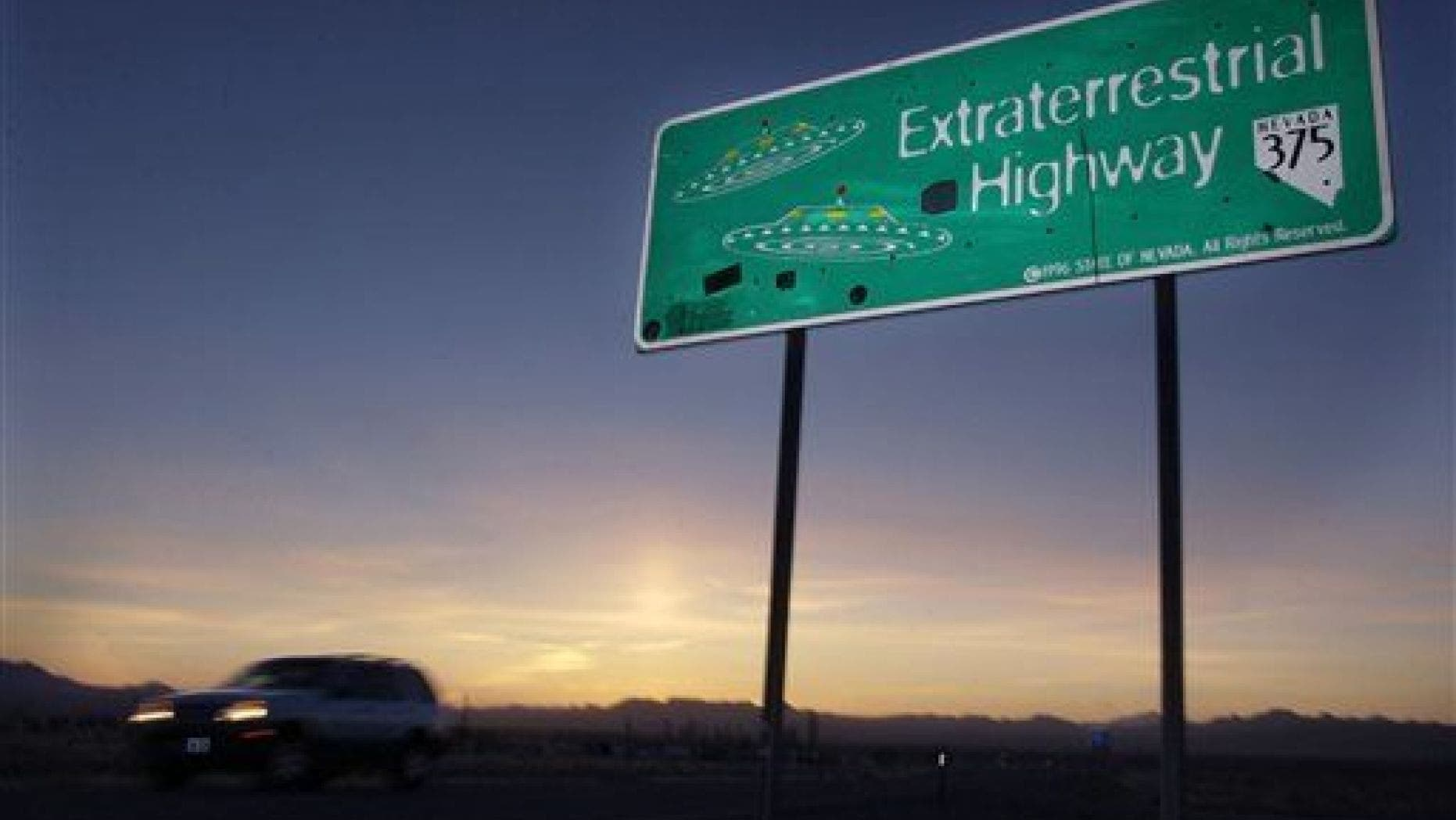 In this April 10, 2002, file photo, a car moves along the Extraterrestrial Highway near Rachel, Nev., the closest town to Area 51. (AP Photo/Laura Rauch, File)