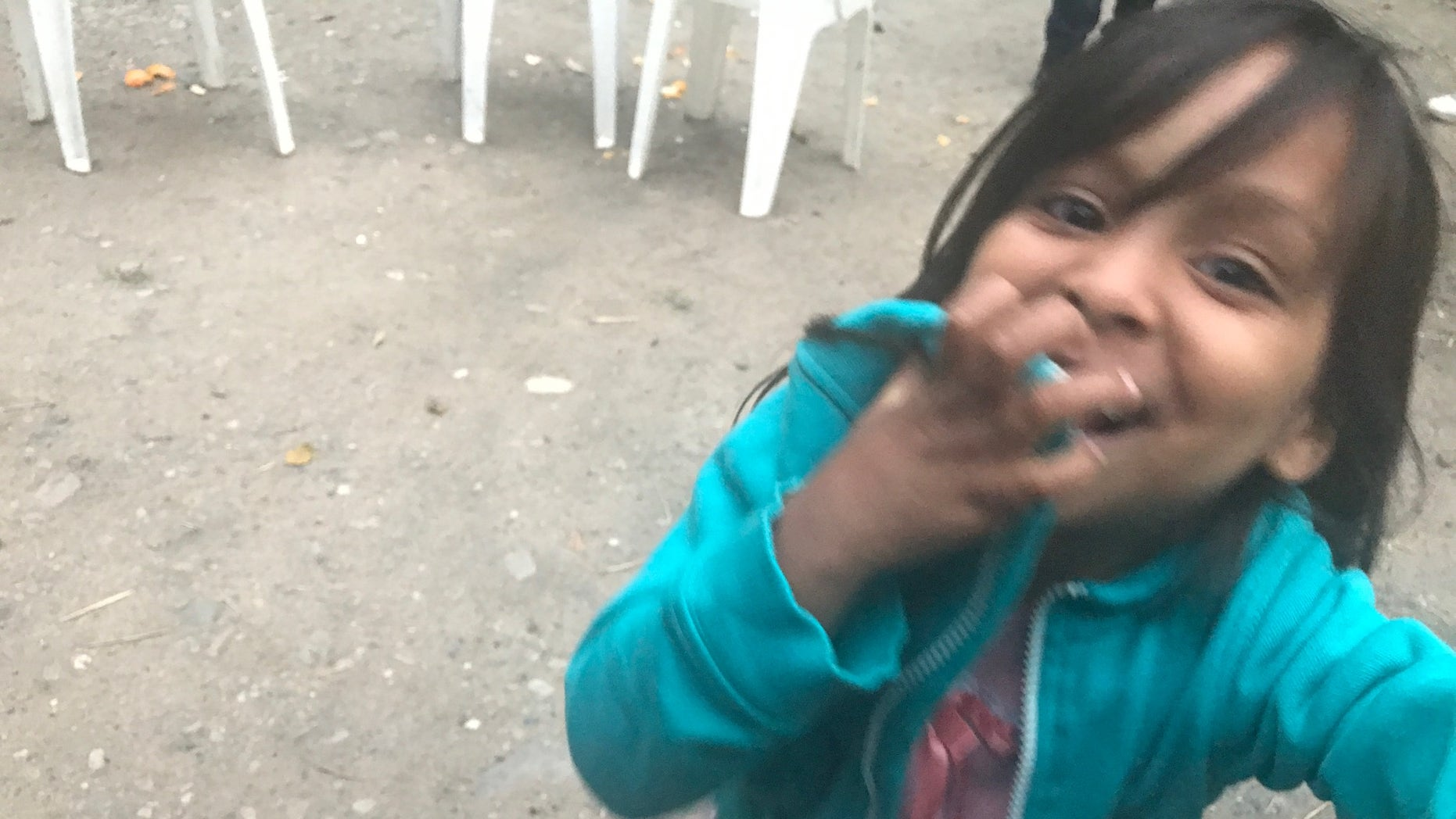 A Venezuelan migrant making the journey through Colombian plays with the only toy she has: her mother's identification card.<br>