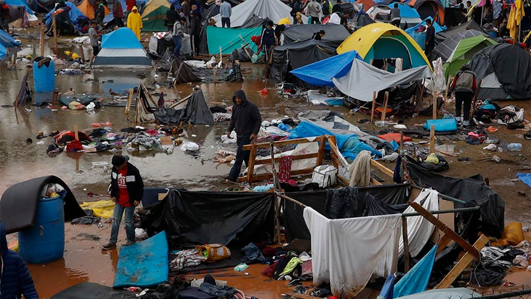 Migrants walk amidst flooded tents after heavy rains poured down on a sports complex that was sheltering thousands of Central Americans in Tijuana, Mexico.