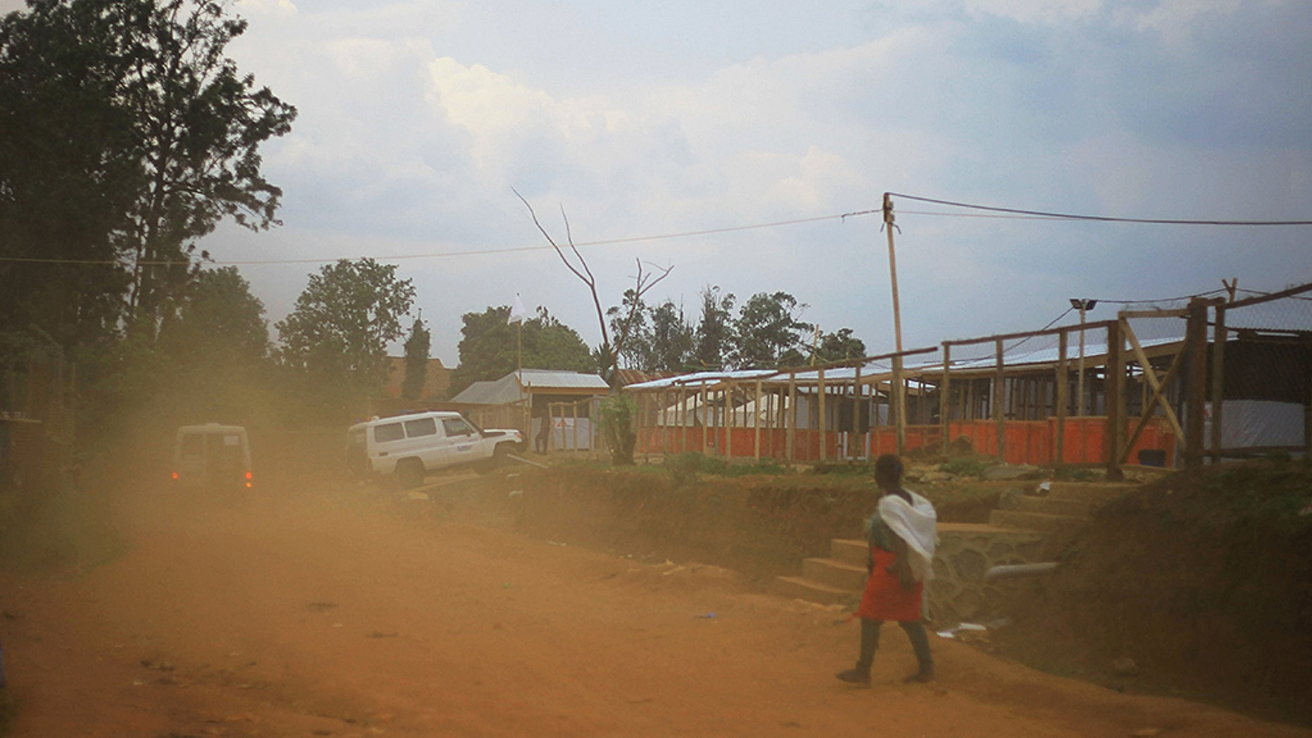 Ambulances drive into an attacked ebola treatment center during protest by demonstrators over their exclusion from the presidential election in Beni, Democratic Republic of the Congo.