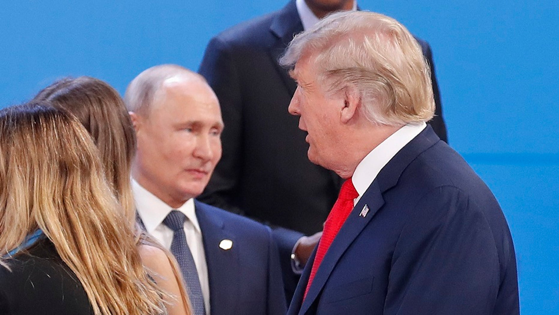 Russia's President Vladimir Putin, left, watches President Donald Trump, right, walk past him as they gather for the group photo at the start of the G20 summit in Buenos Aires, Argentina.