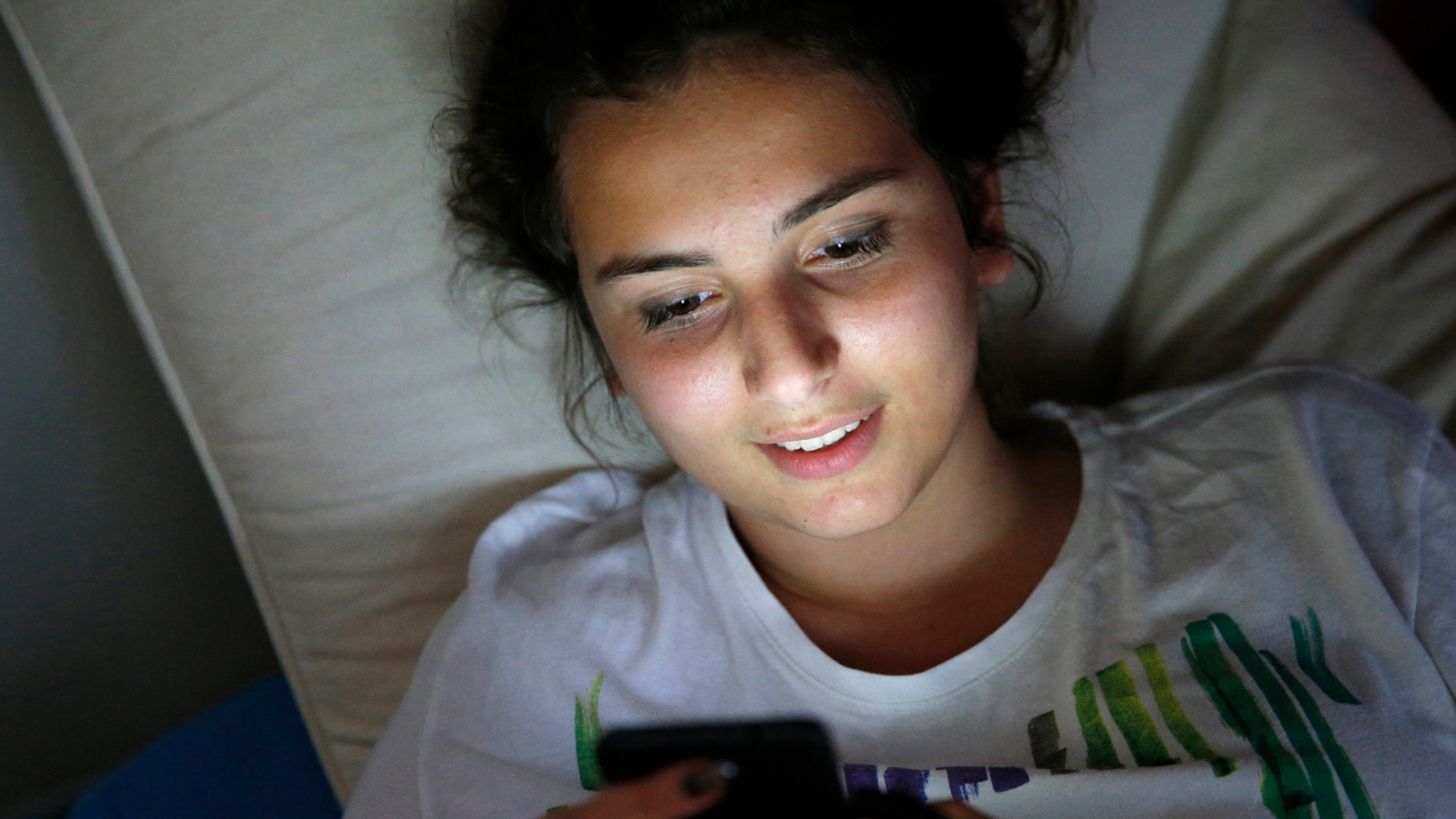 Teenager using a cell phone on her bed (Photo by: Godong/UIG via Getty Images)