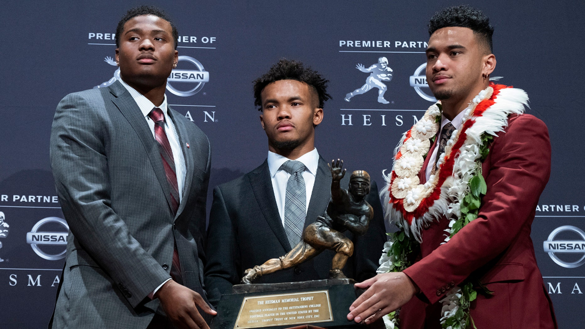 Heisman Trophy finalists, from left, Dwayne Haskins, from Ohio State; Kyler Murray, from Oklahoma; and Tua Tagovailoa, from Alabama, pose with the trophy during a media event Saturday, Dec. 8, 2018, in New York. (AP Photo/Craig Ruttle)