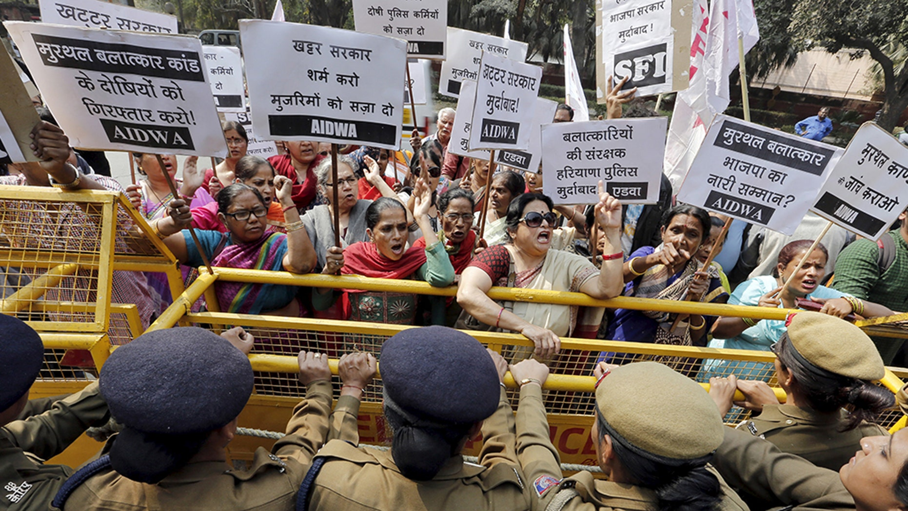 Activists from All India Democratic Women's Association shout slogans behind a police barricade outside the Haryana Bhawan during a protest in New Delhi, India. (Reuters)