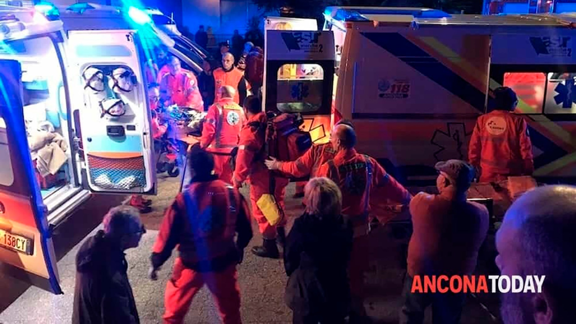 Rescuers assist injured people outside a nightclub in Corinaldo, central Italy, early Saturday, Dec. 8, 2018. (Stefano Pagliarini/Ancona Today via AP)