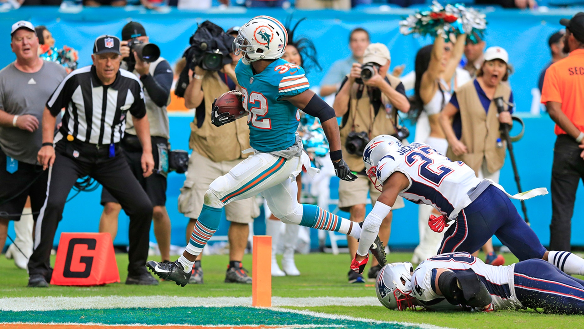 Miami Dolphins running back Kenyan Drake (32) scores to defeat the New England Patriots at Hard Rock Stadium in Miami Gardens on Sunday.