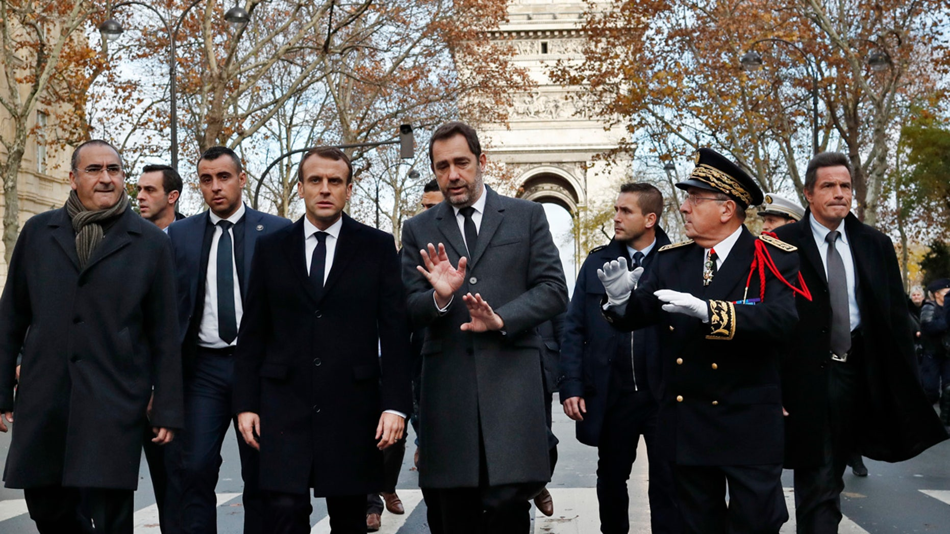 France's President Emmanuel Macron, centre left, France's Interior Minister Christophe Castaner, center, Secretary of State to a Interior Minister Laurent Nunez, left, and Paris military Prefect Michel Delpuech, right, arrive to revisit firefighters and proof military officers a day after a demonstration, in Paris, Sunday, Dec. 2, 2018. (AP Photo/Thibault Camus)