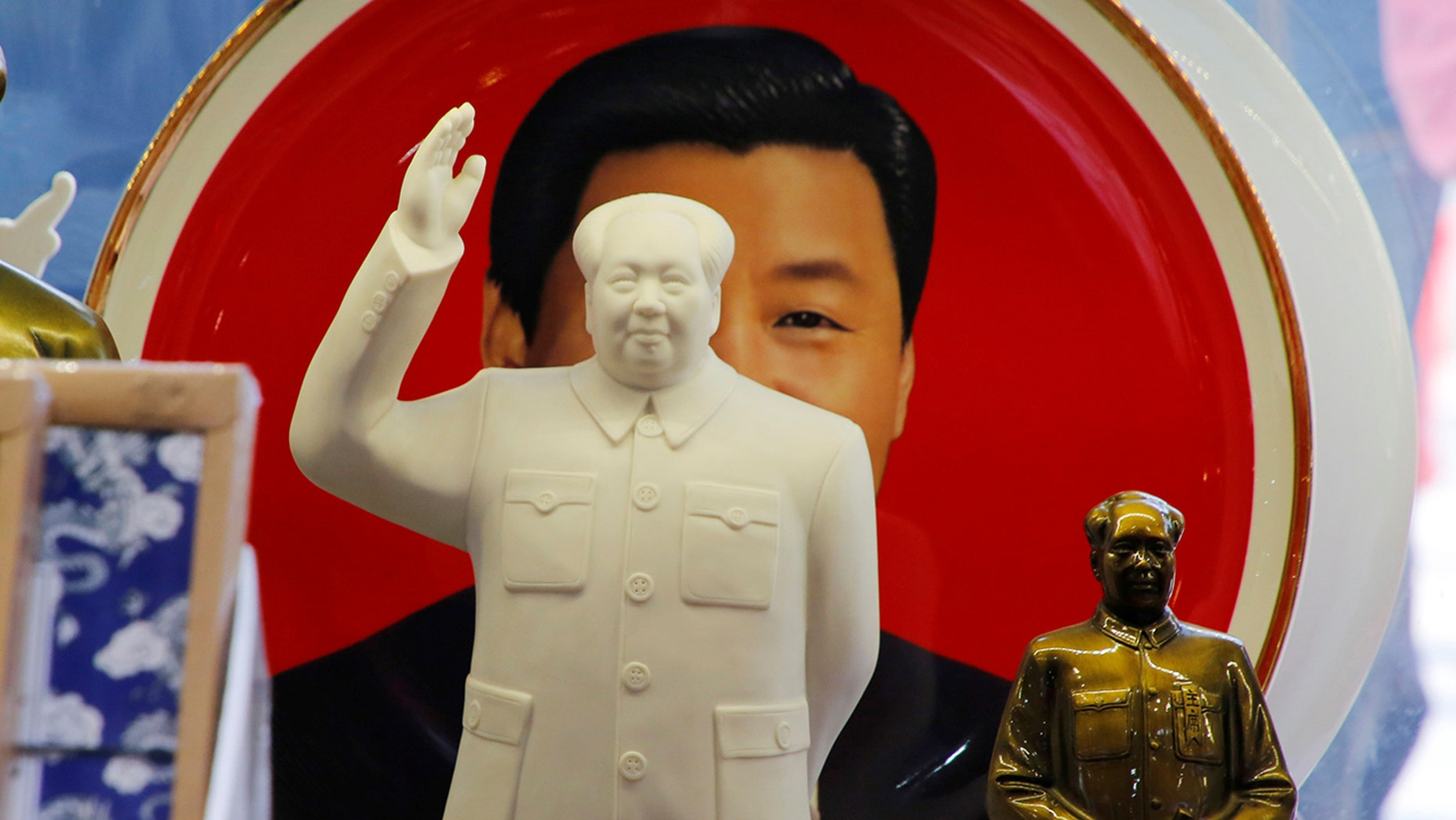 Sculptures of the late Chinese Chairman Mao Zedong are placed in front of a souvenir plate featuring a portrait of Chinese President Xi Jinping at a shop next to Tiananmen Square in Beijing, China.