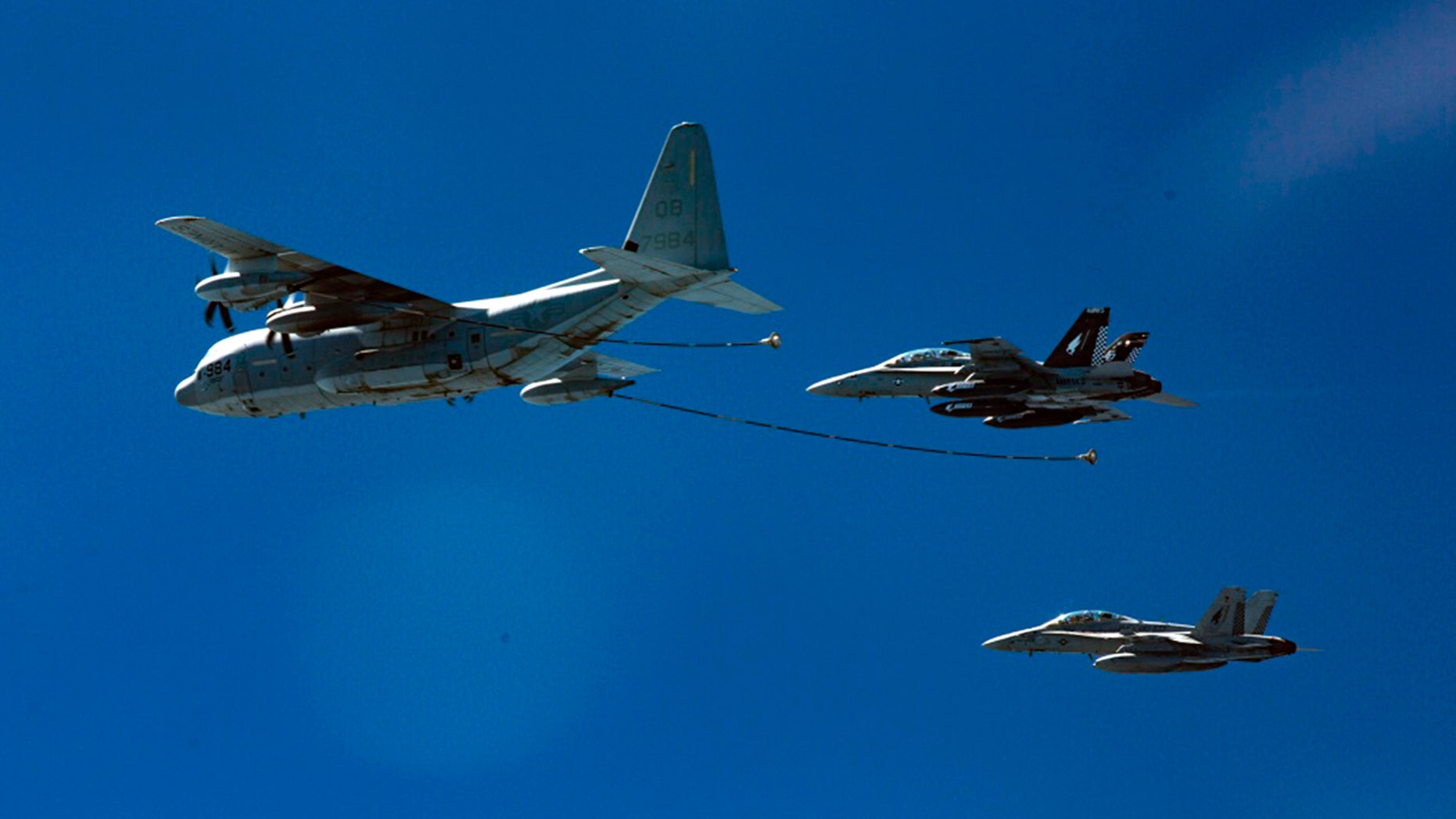 Two F/A-18D Hornets with Marine All-Weather Fighter Attack Squadron 533 approach a KC-130J with Marine Aerial Refueler Transport Squadron 352 during a Special Purpose Marine Air-Ground Task Force - Crisis Response - Central Command aerial refueling exercise in undisclosed location. (Cpl. Trever Statz/U.S. Marine Corps via AP)