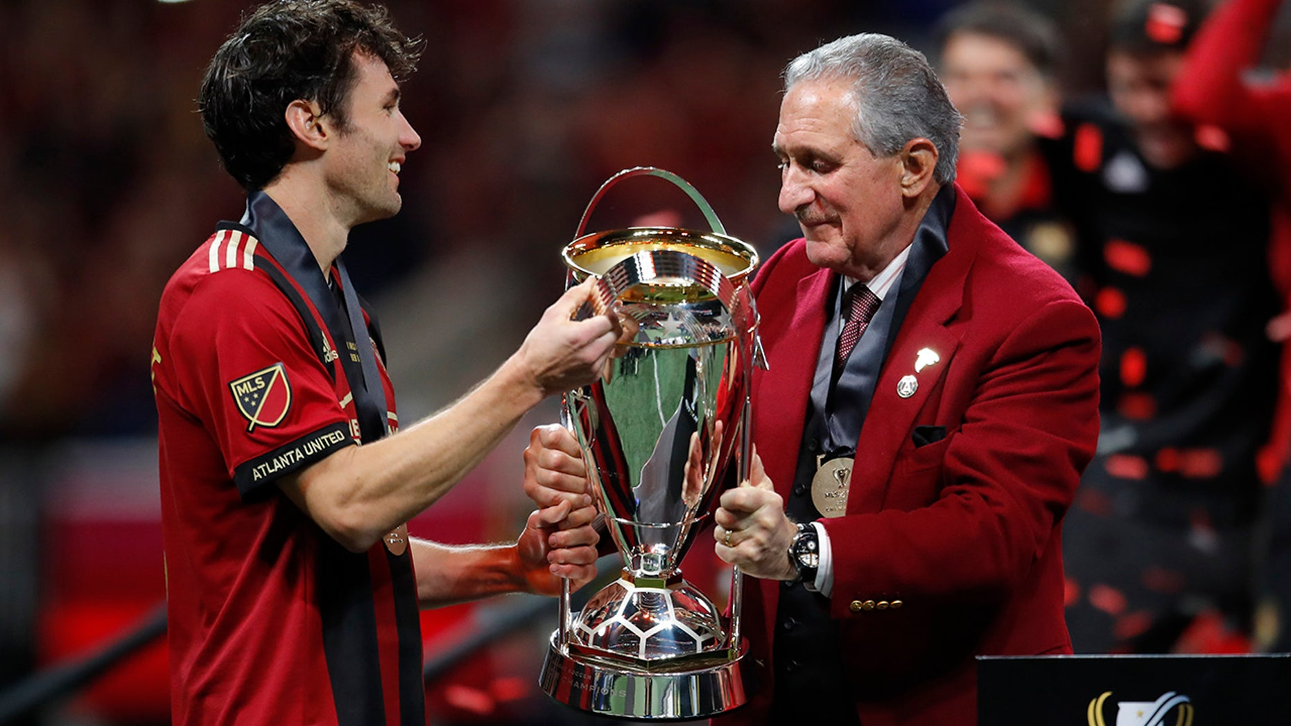 Atlanta United owner Arthur Blank, right, hands the trophy to team captain Michael Parkhurst (3) after the MLS Cup championship soccer game against the Portland Timbers, Saturday, Dec. 8, 2018, in Atlanta. Atlanta United won 2-0. (AP Photo/Todd Kirkland)