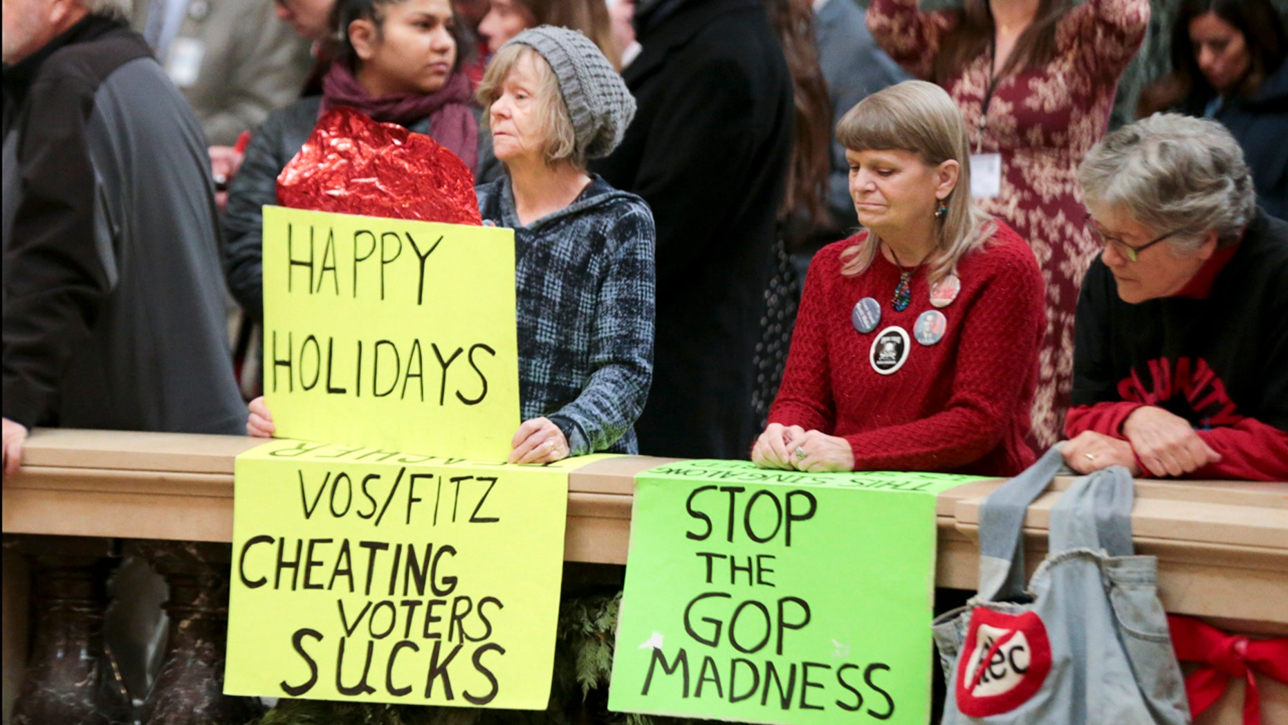 Protesters Peppi Elder, left, and Christine Taylor holding up signs during the state Christmas Tree lighting ceremony in Madison, Wisconsin.