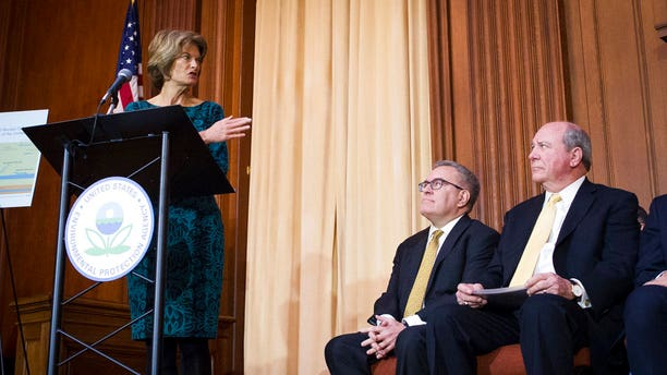 """Sen. Lisa Murkowski, R-Alaska, gesturing towards Acting EPA Administrator Andrew Wheeler, center, and Assistant Secretary of the Army for Civil Works Rickey """"RD"""" James, after Wheeler signed an order withdrawing federal protections for countless waterways and wetlands. (AP Photo/Cliff Owen)"""