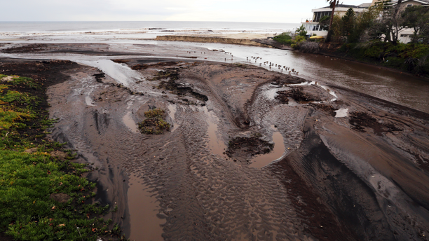 Mud and debris fill the outfall where Trancas Creek flows into the Pacific Ocean in an area burned by the Woolsey fire in Malibu, Calif. Thursday, Dec. 6, 2018. The second round of a fall storm is causing flooding on Los Angeles-area roads. Snow has forced the closure of Interstate 5 in the Grapevine area between Los Angeles and the San Joaquin Valley. Closer to sea level, the system dumped rain that flooded highways and caused nightmare traffic conditions for commuters. (AP Photo/Reed Saxon)