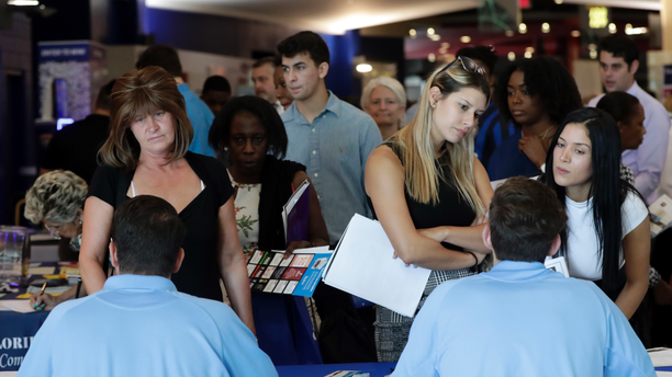 FILE- In this June 21, 2018 file photo, job applicants talks with representatives from Aldi at a job fair hosted by Job News South Florida, in Sunrise, Fla. On Thursday, Dec. 6, payroll processor ADP reports how many jobs private employers added in November. (AP Photo/Lynne Sladky, File)