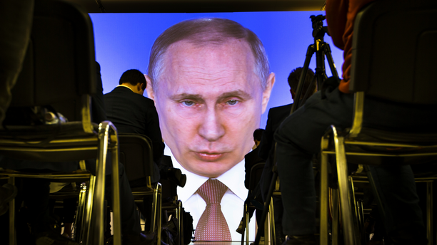 Journalists watch as Russian President Vladimir Putin gives his annual state of the nation address in Manezh in Moscow, Russia, on March 1, 2018. (AP Photo/Alexander Zemlianichenko)