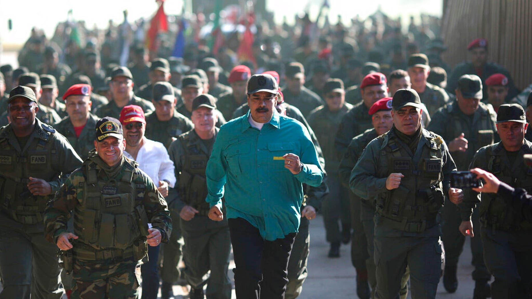 In this photo released to the media by the Miraflores presidential palace press office, Venezuelan President Nicolas Maduro jogs ahead of soldiers during a visit last month to Carabobo State. (Marcelo Garcia/Miraflores presidential palace press office via AP)