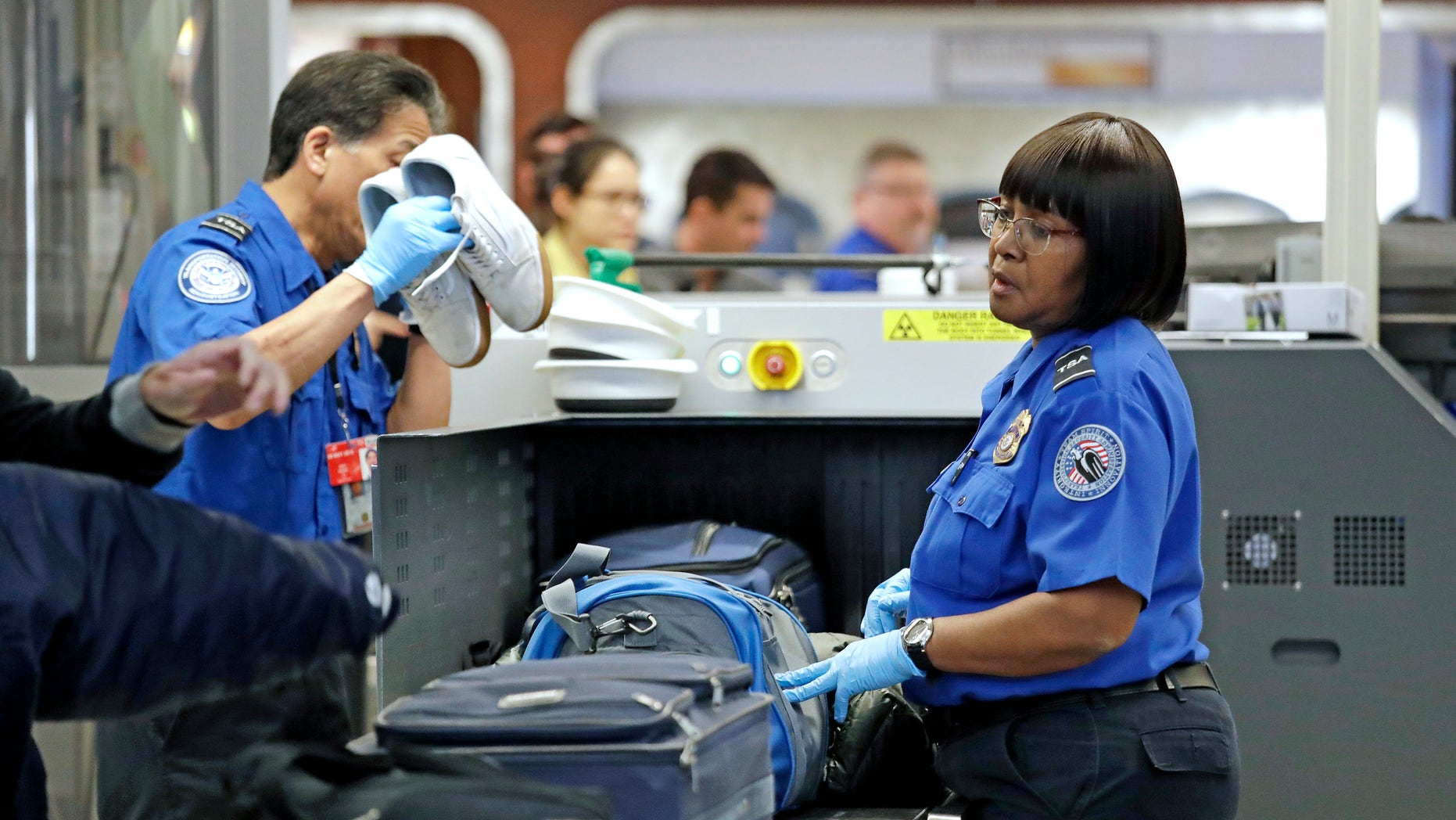 Transportation Security Administration (TSA) officers assist travelers with luggage through a security screening area during a partial federal government shutdown Monday, Dec. 31, 2018, at Seattle-Tacoma International Airport in Washington state. (Associated Press)