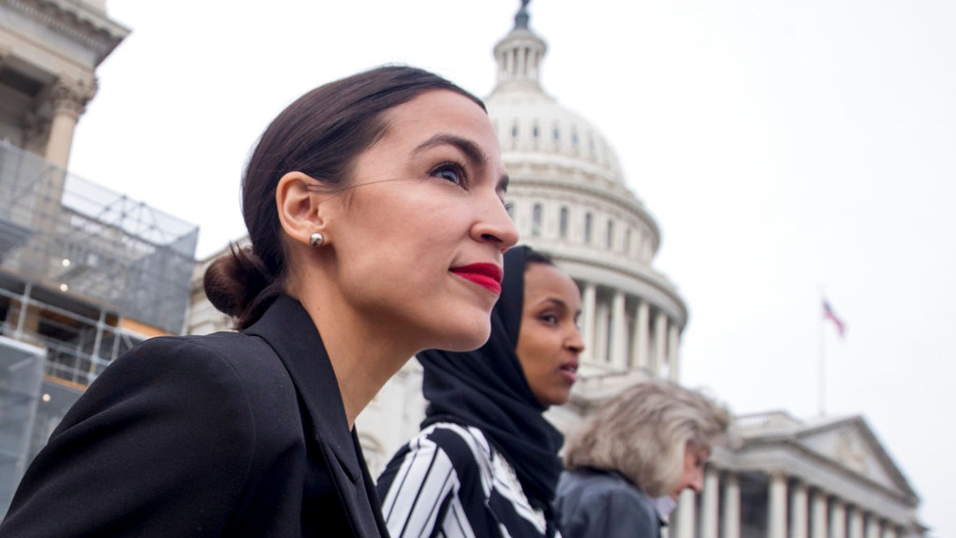 Rep. Alexandria Ocasio-Cortez, left, and D-N.Y., Rep. Ilhan Omar, D-Minn., center, walk down the House steps.