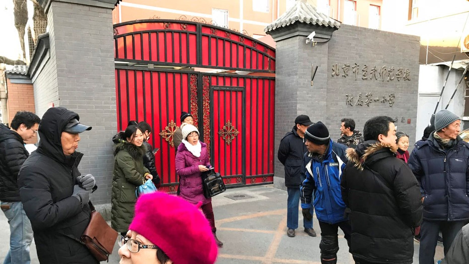 Parents gather at an entrance gate to the Beijing No. 1 Affiliated Elementary School of Xuanwu Normal School following an attack in Beijing, China, Tuesday, Jan. 8, 2019.