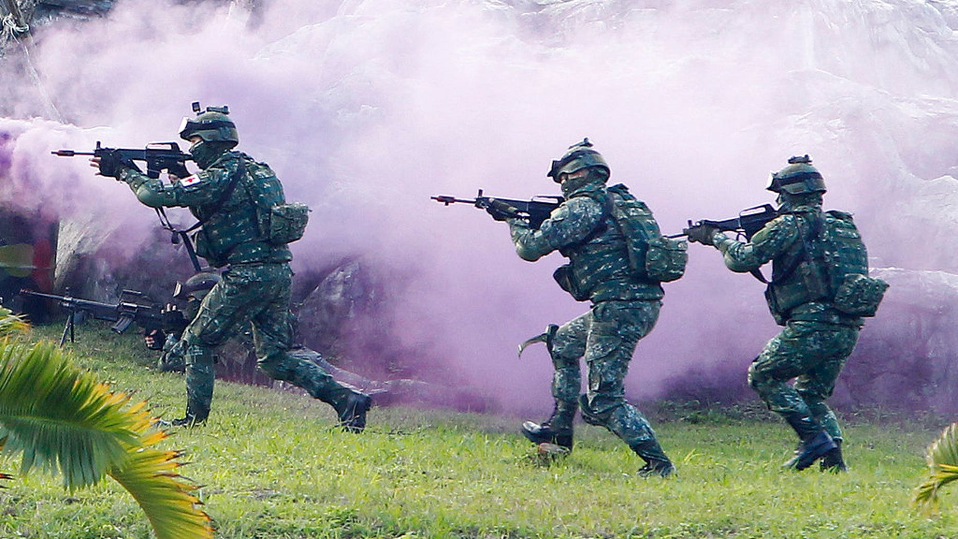 FILE: Soldiers from Taiwan's special forces move through colored smoke during a military exercise in Taipei, Taiwan. (AP Photo/Chiang Ying-ying)